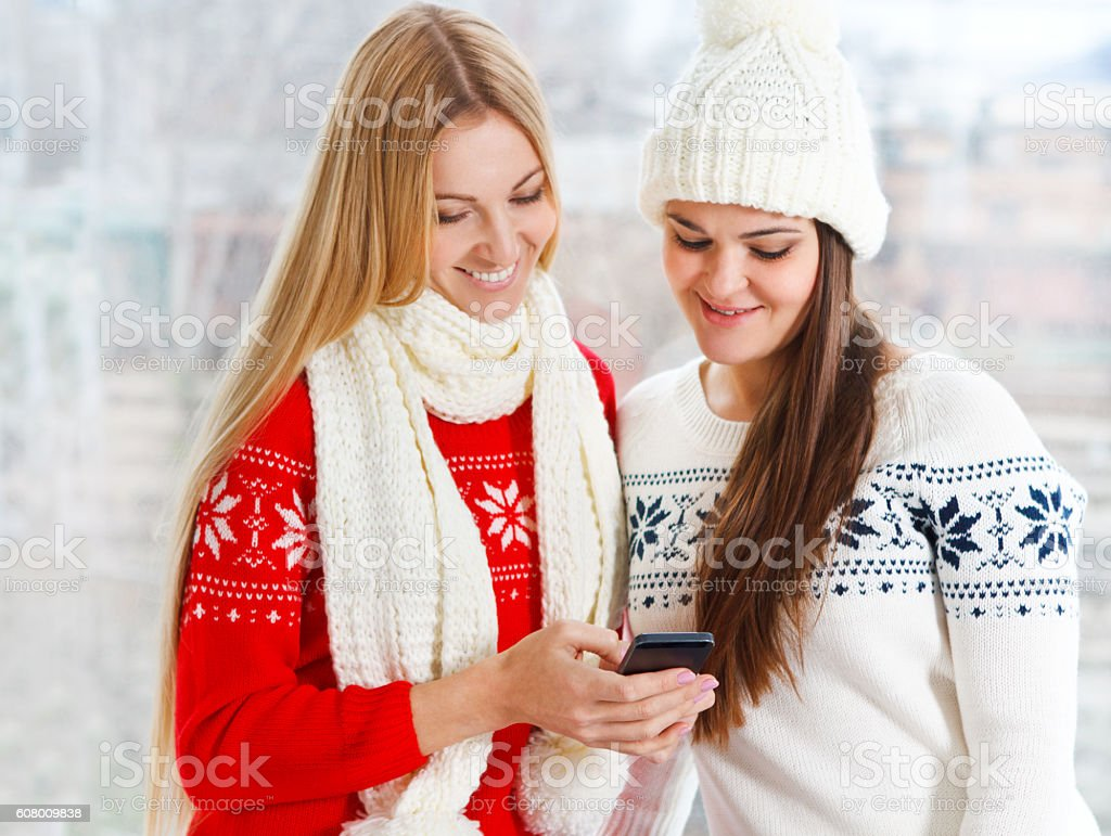 Happy girls using app on a mobile phone stock photo