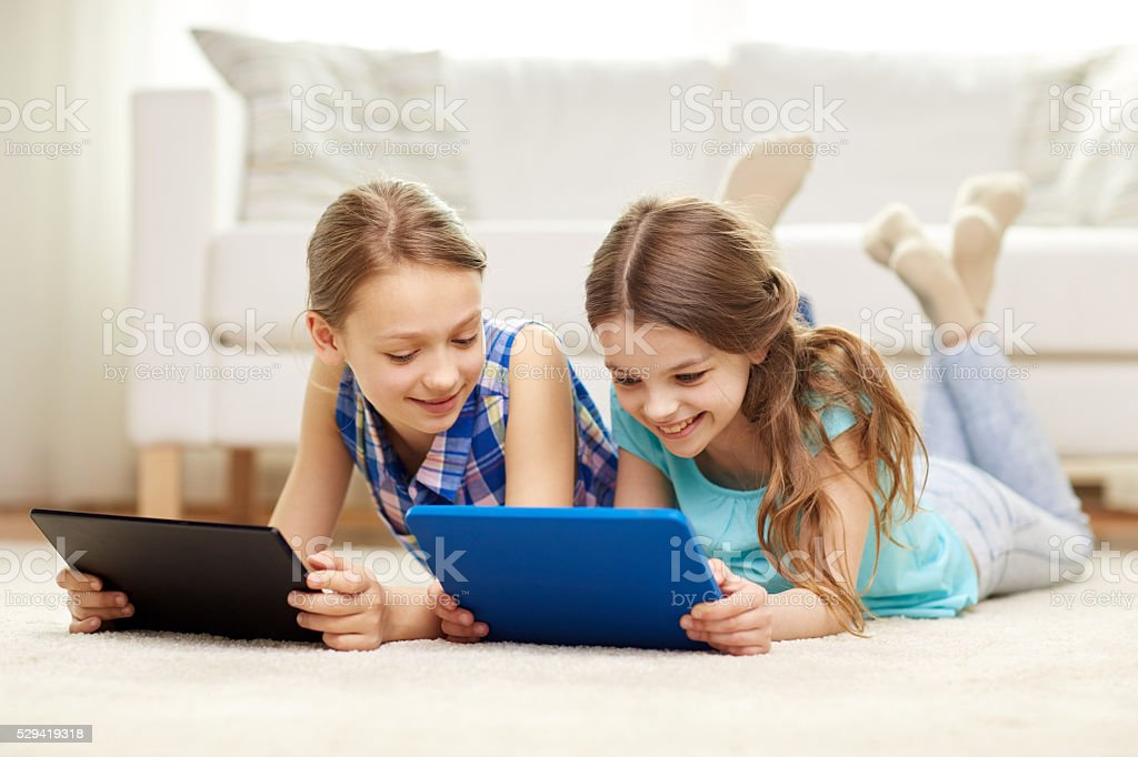 happy girls with tablet pc lying on floor at home stock photo