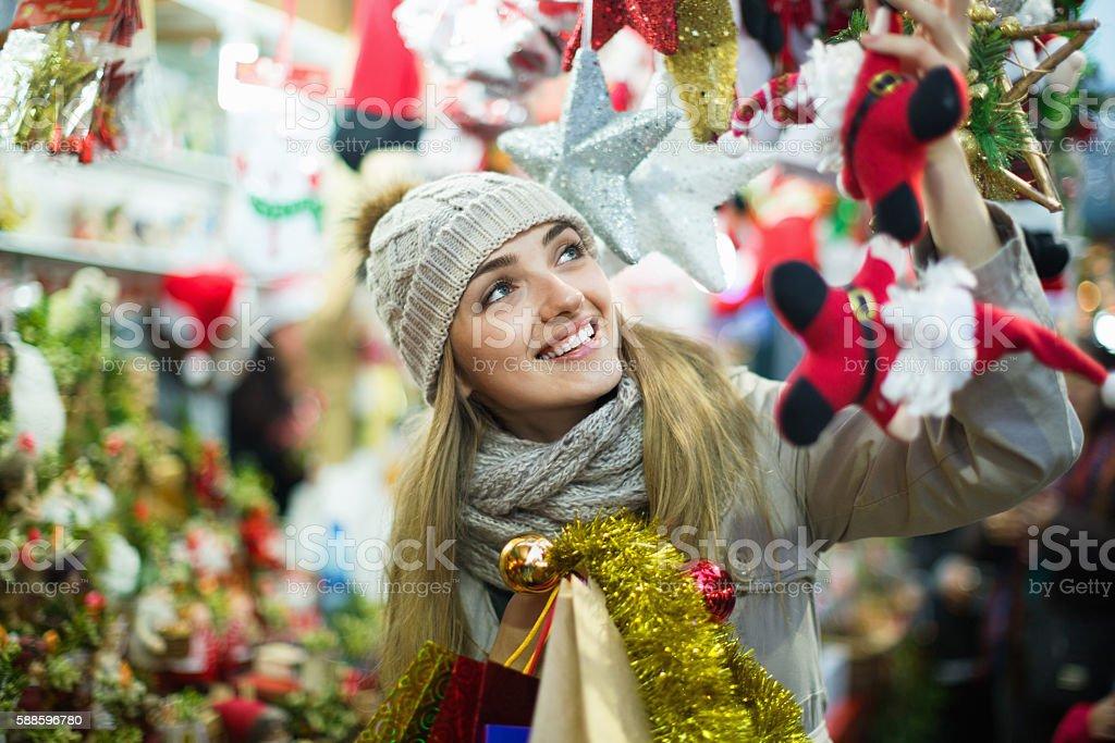 Happy glad cheerful girl choosing Christmas decoration stock photo