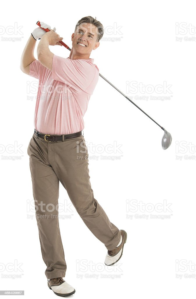 Happy Golfer Looking Away While Swinging Golf Club stock photo