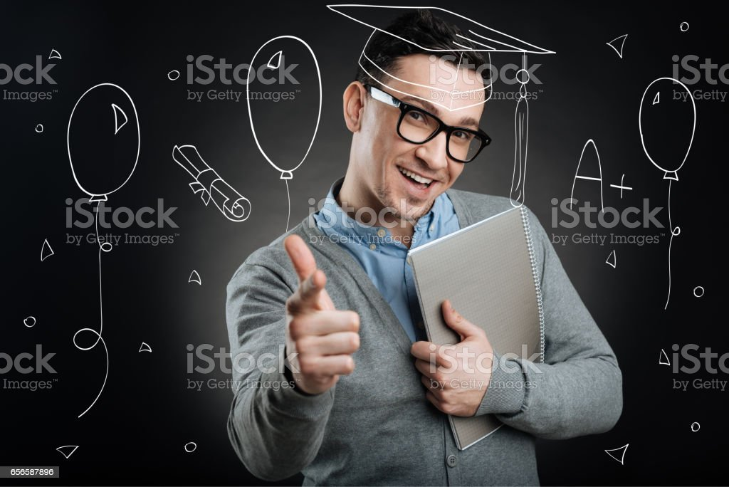 Happy graduate. Happy African man in graduation gowns holdin stock photo