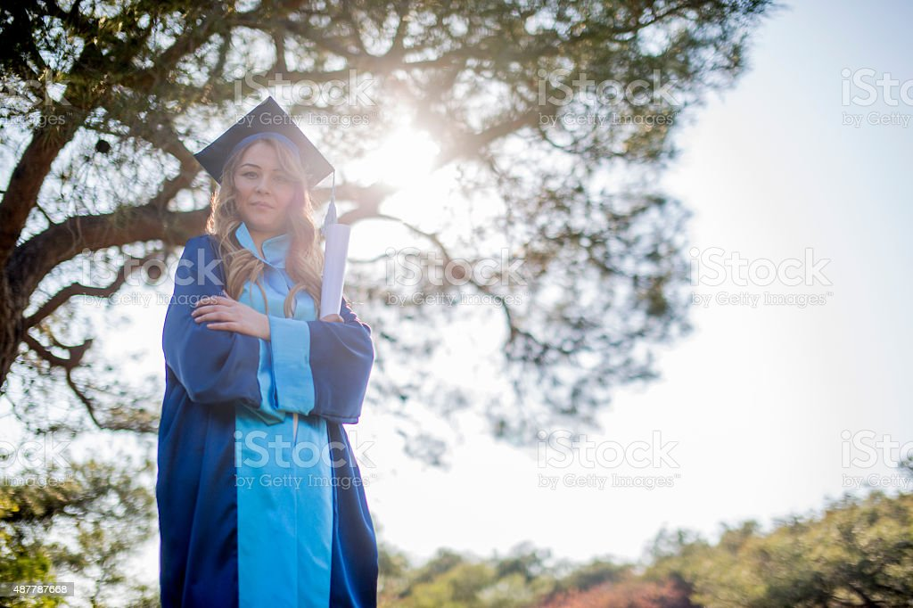 Happy Graduating Mixed Race Woman In Cap and Gown Celebrating stock photo