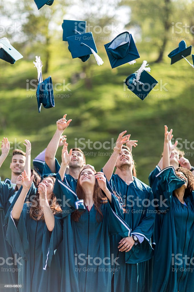 Happy graduation students throwing mortar board hats in the air. stock photo