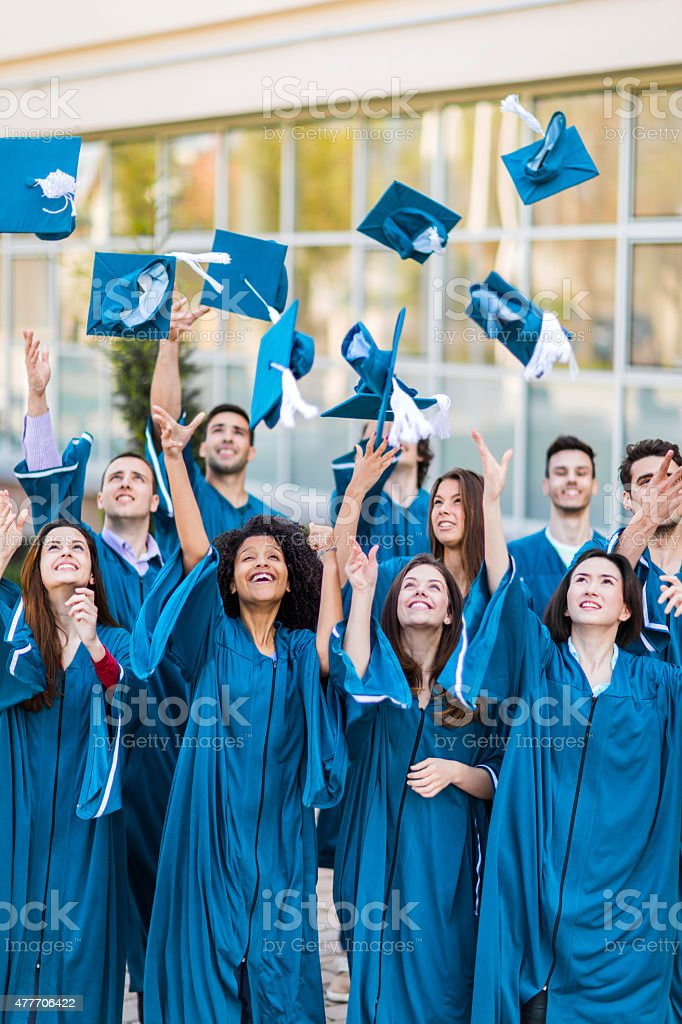 Happy graduation students throwing mortarboard hats in the air. stock photo