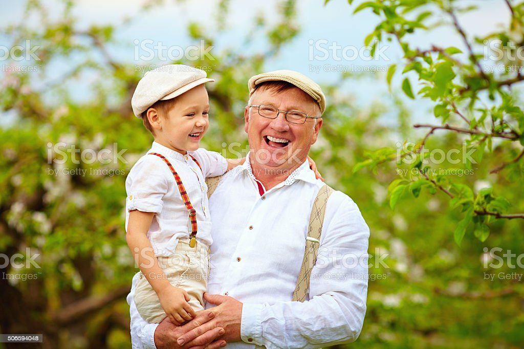 happy grandfather and grandson having fun in spring garden stock photo