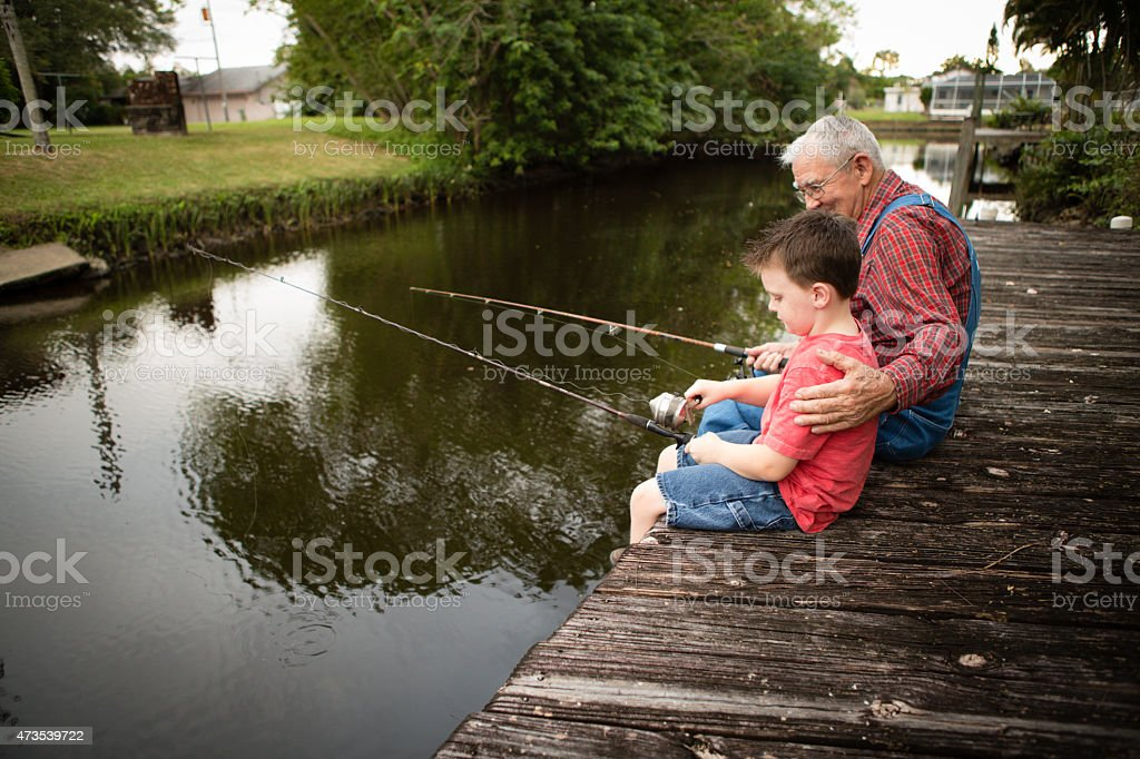Happy Grandfather and Great Grandson Fishing on Dock stock photo