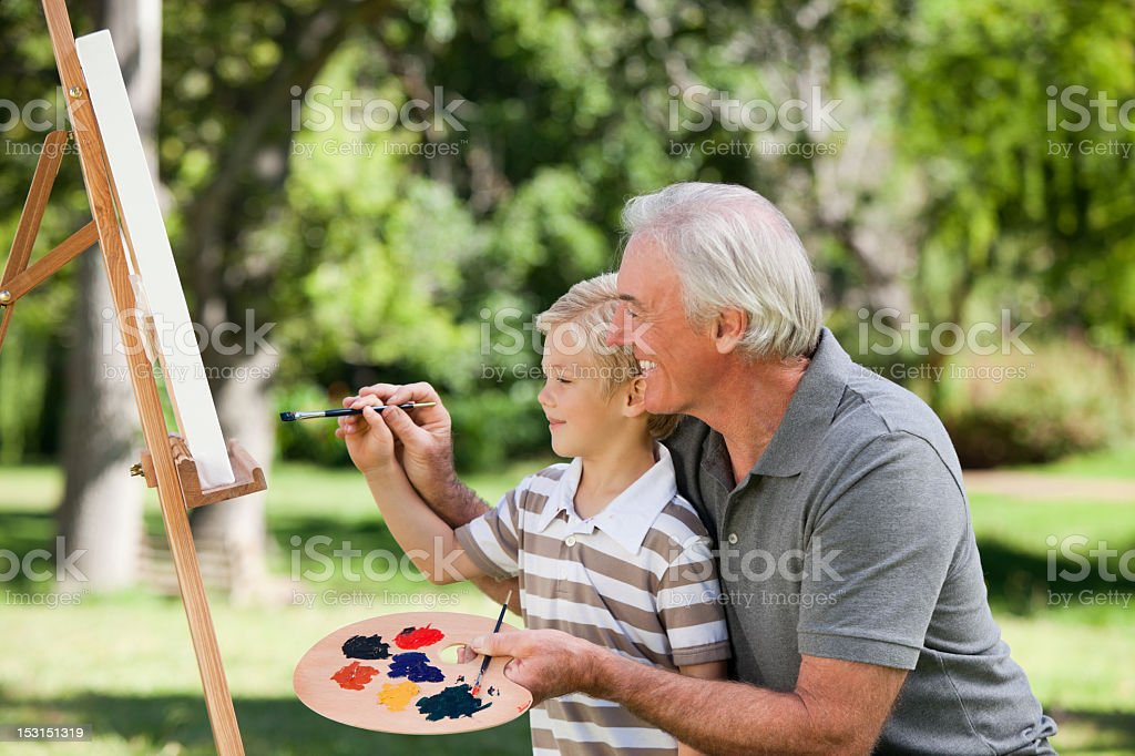 Happy Grandfather and his grandson painting in the garden royalty-free stock photo