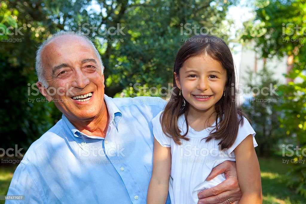 A happy grandfather holding a girl and smiling royalty-free stock photo