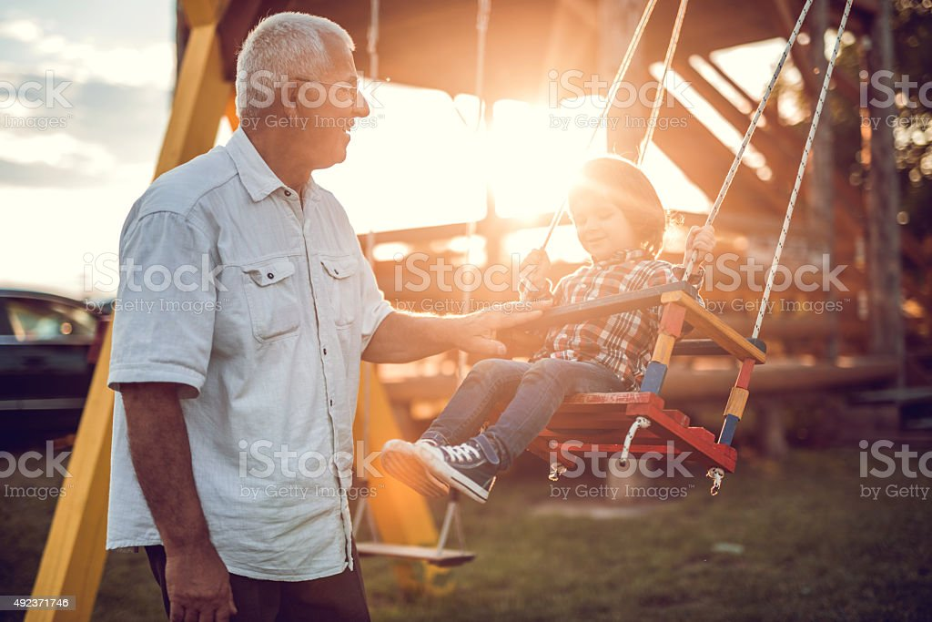Happy grandfather swinging his grandson at sunset. stock photo