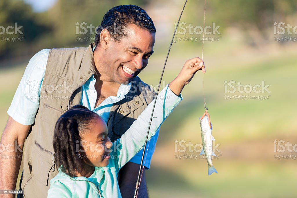 Happy grandfather teaches granddaughter to fish stock photo