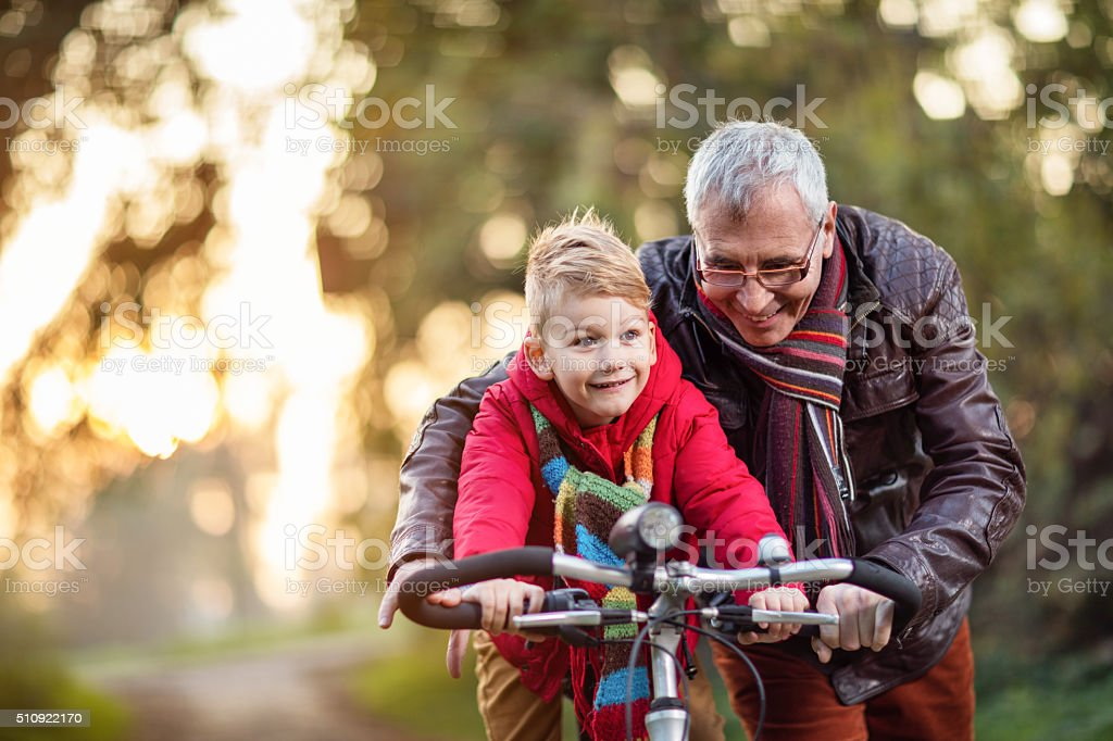 Happy grandfather teaching his grandson how to ride a bike. stock photo