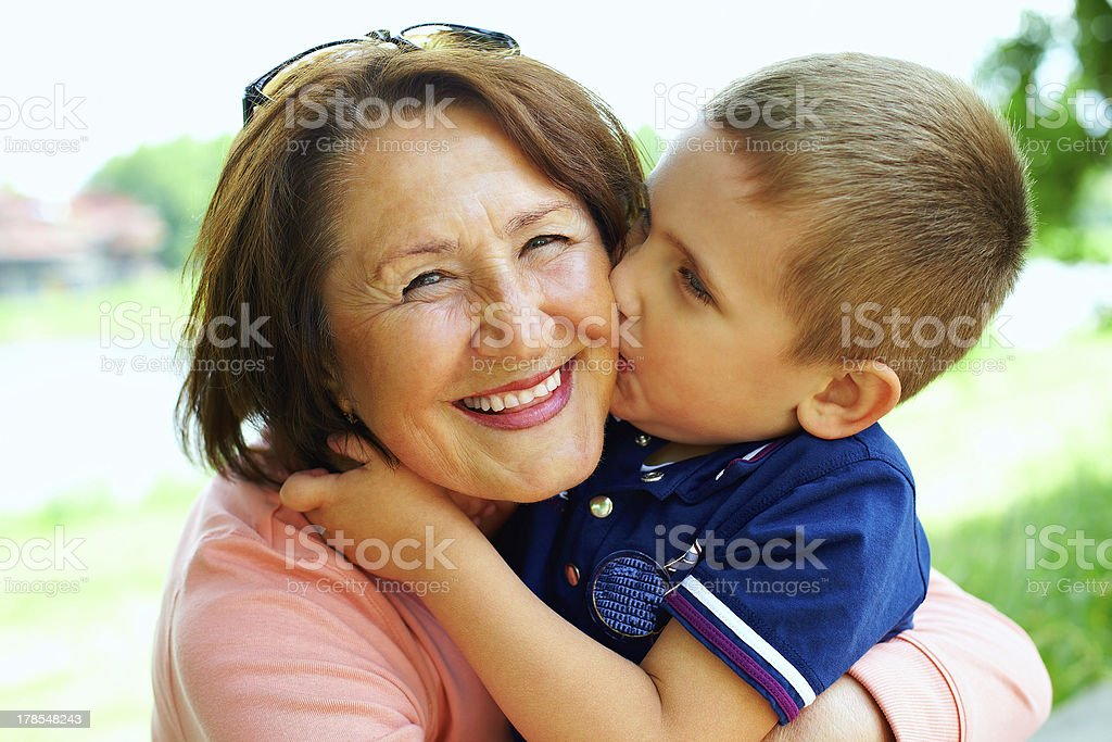happy grandma with grandson embracing outdoor stock photo