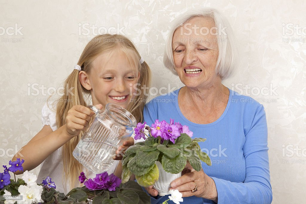 Happy Grandmother and Granddaughter Care about Violet in Flowerpot. royalty-free stock photo