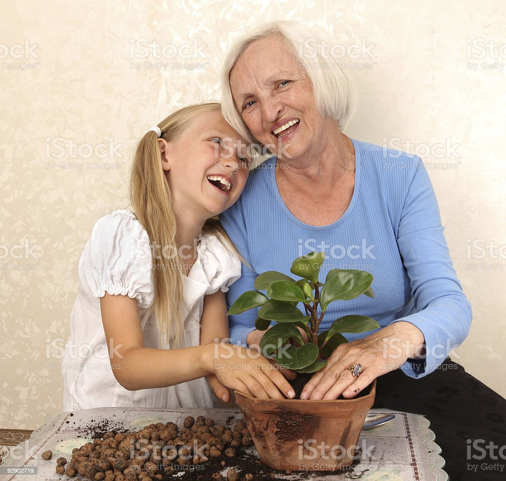 Happy Grandmother and Granddaughter Planting a Flower in Flowerpots. royalty-free stock photo