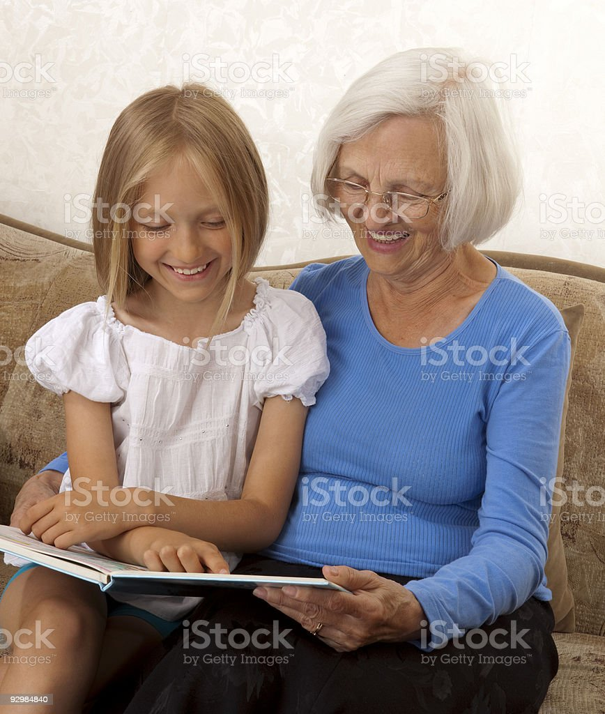 Happy Grandmother and Granddaughter Reading a Book Together. royalty-free stock photo