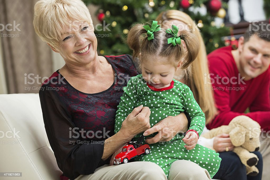 Happy grandmother playing with toddler grandchild on Christmas day stock photo