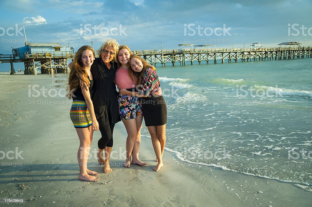 Happy grandmother with her three lovely grandaugthers on the beach. royalty-free stock photo