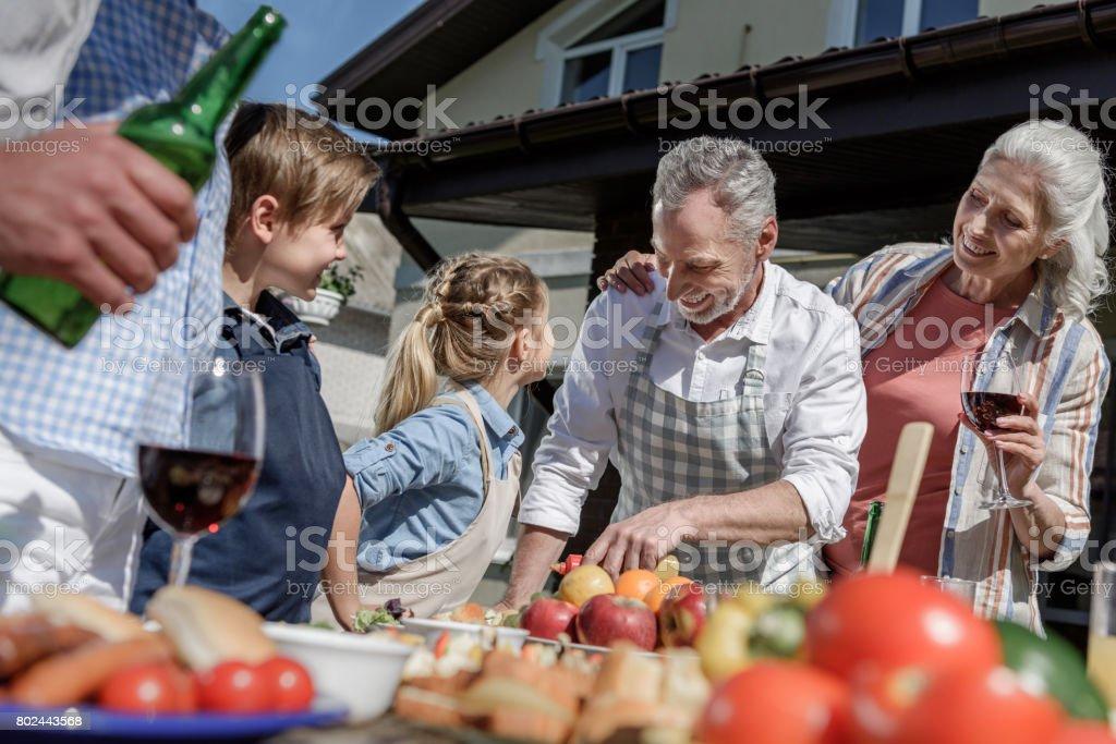 happy grandparents and grandchildren preparing food on picnic outdoors stock photo