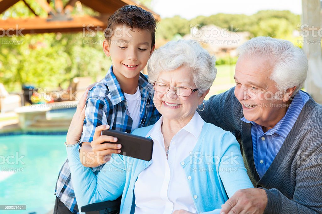 Happy grandparents and grandson take selfie with smartphone stock photo