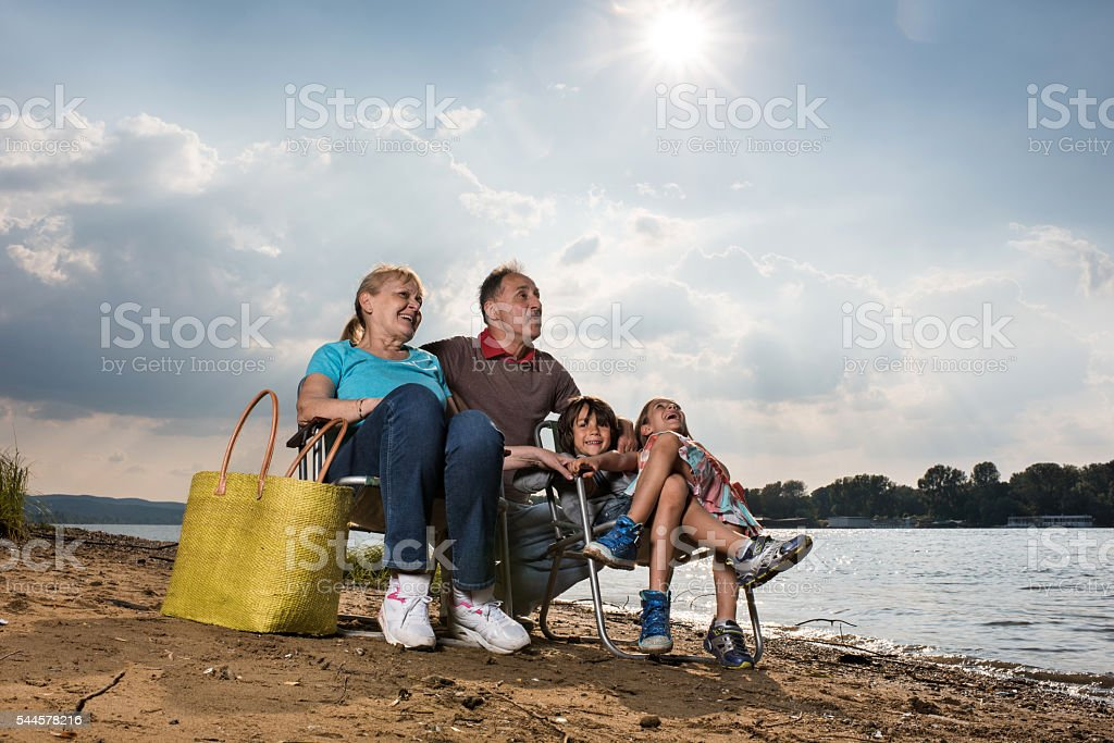 Happy grandparents and their grandchildren relaxing by the river. stock photo