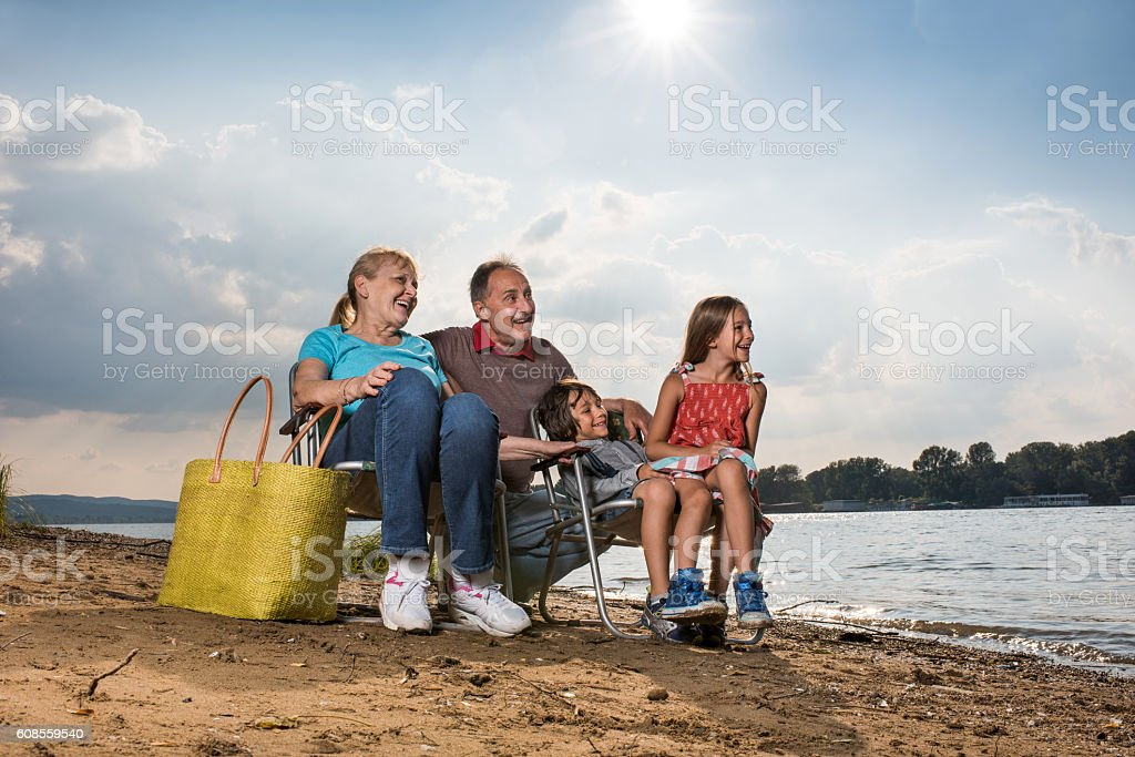 Happy grandparents and their grandchildren relaxing near the river. stock photo