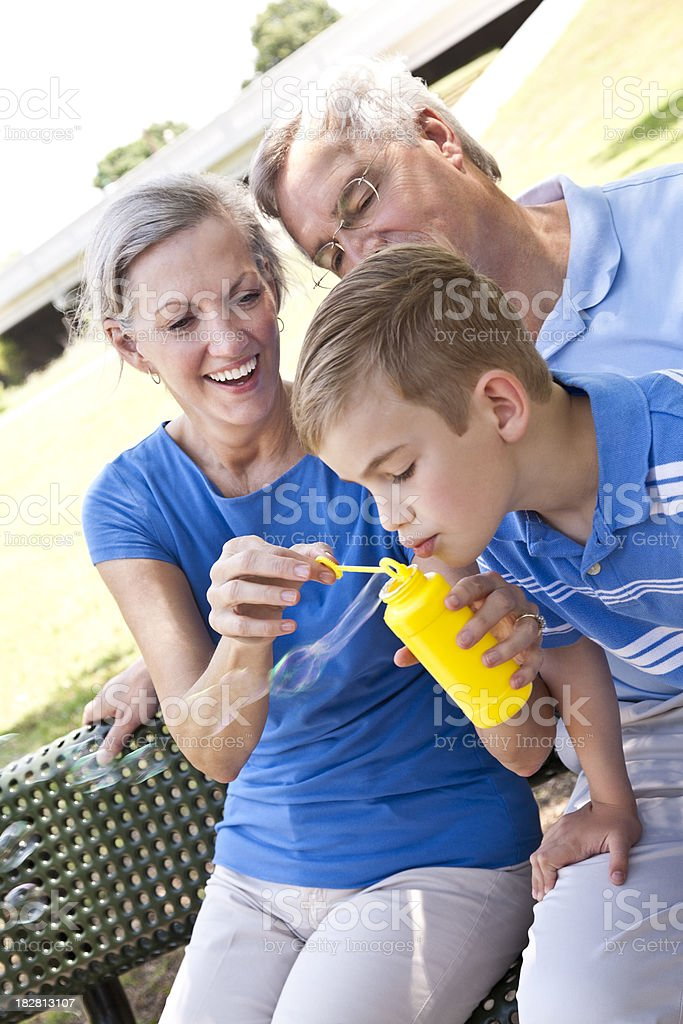 Happy Grandparents Playing Bubbles With Their Grandson royalty-free stock photo