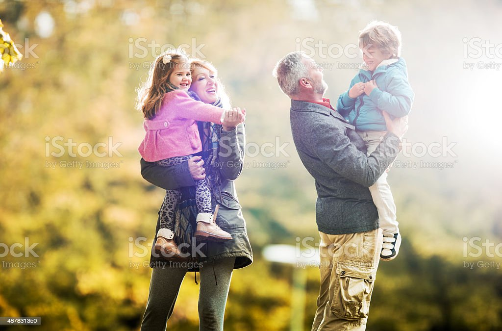 Happy grandparents playing with their grandchildren in nature. stock photo