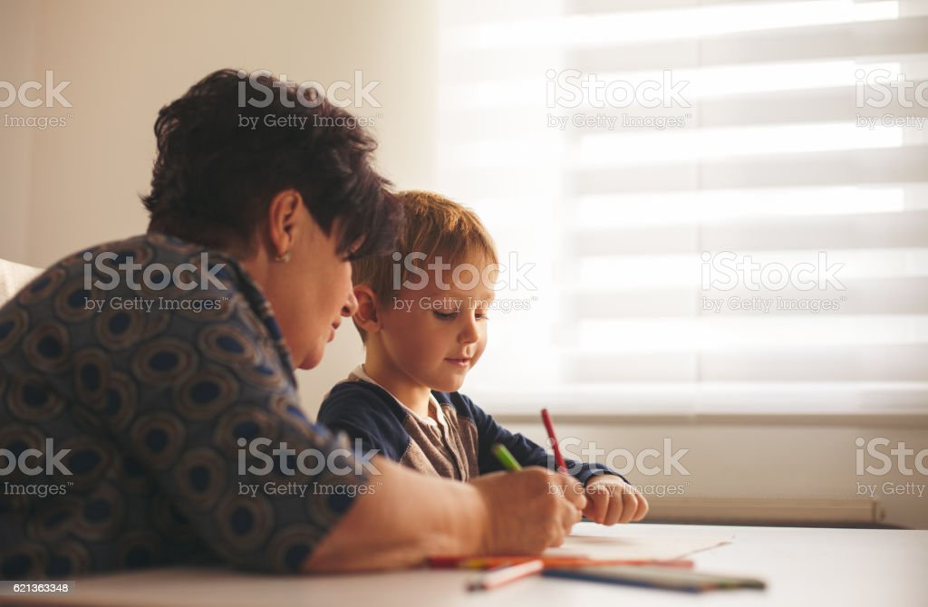 Happy grandson and grandmother drawing together at home stock photo