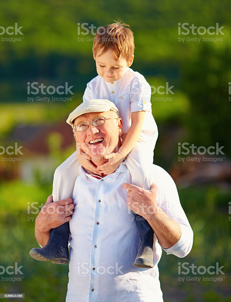 happy grandson sitting on shoulders of grandpa, countryside stock photo