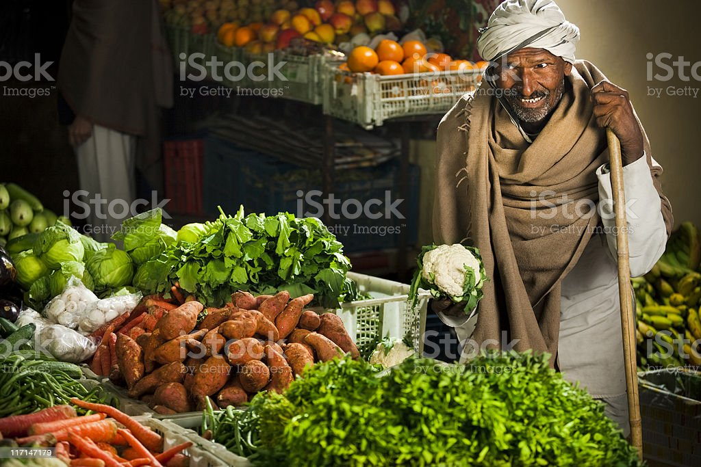 Happy greengrocer selling vegetables and fruits at his shop. stock photo