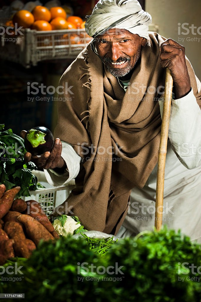 Happy greengrocer selling vegetables and fruits at his shop stock photo