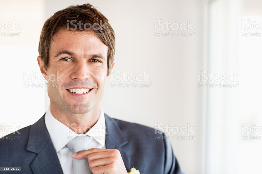Happy Groom Adjusting Tie At Home stock photo