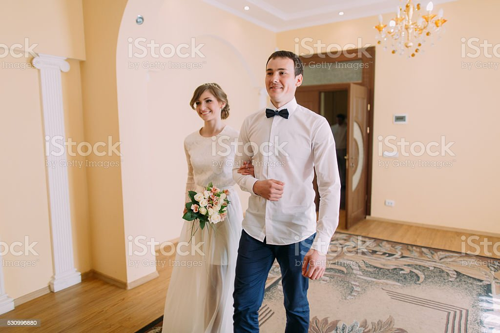 Happy groom and bride walking hand-in-hand  at civil stock photo