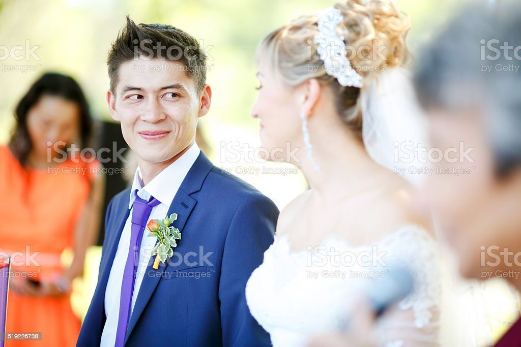Happy groom is looking at bride during wedding ceremony stock photo