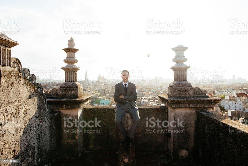 Happy groom sitting on a rooftop in Havana Cuba stock photo