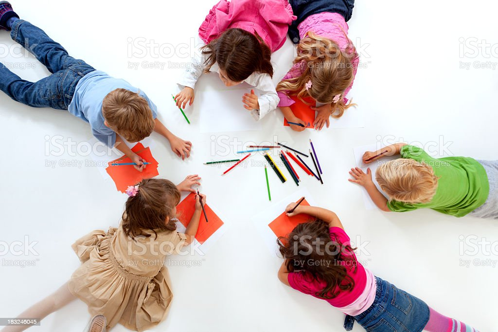 Happy group of children lying down in circle and drawing royalty-free stock photo