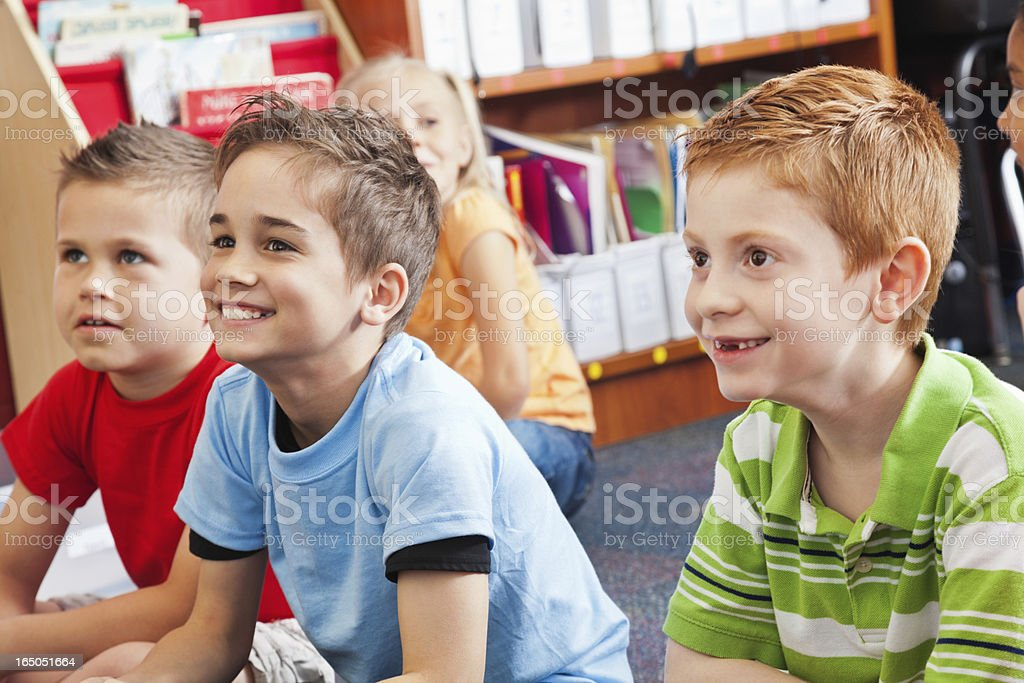 Happy group of elementary age kids listening to story royalty-free stock photo