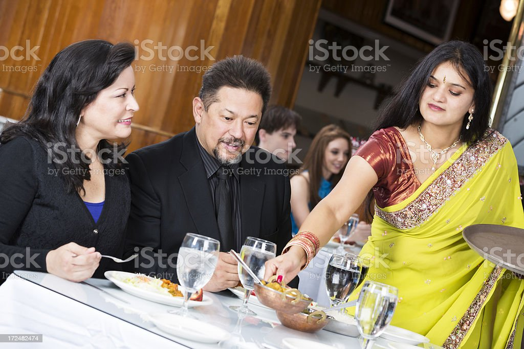 Happy group of friends at an indian restaurant being served royalty-free stock photo