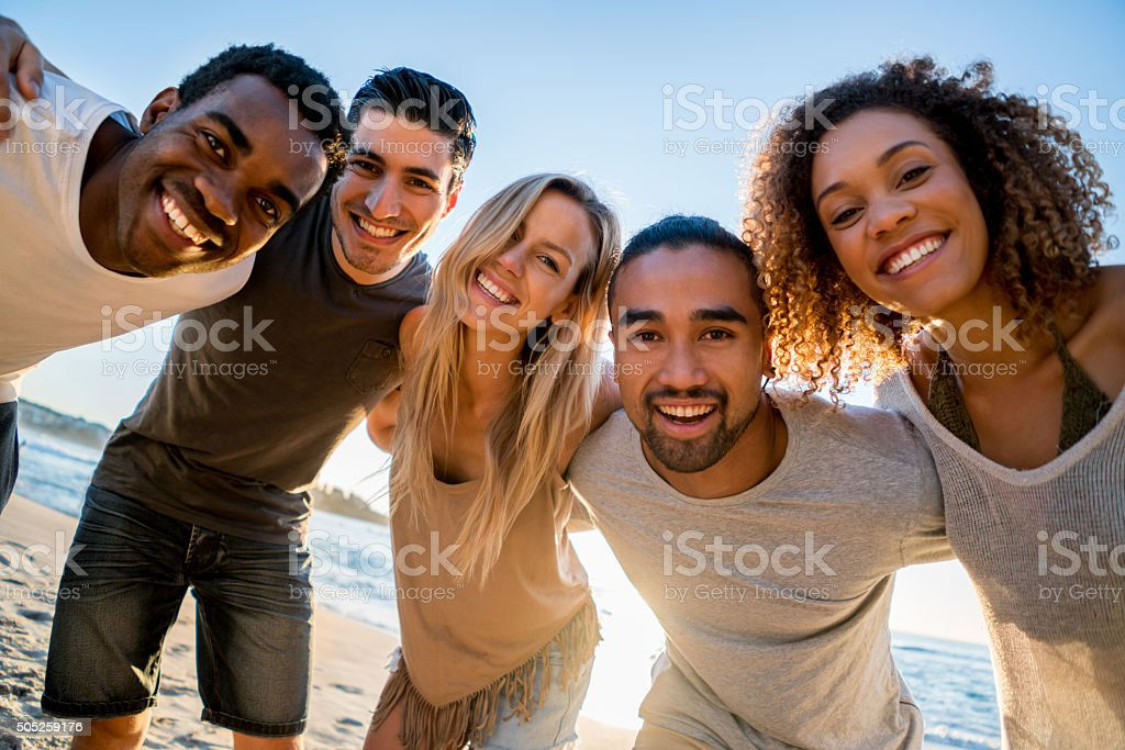 Happy group of friends at the beach stock photo