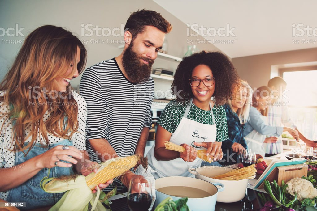 Happy group of friends cooking together at home stock photo