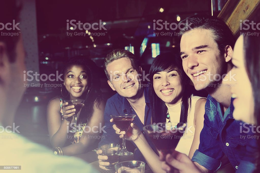 Happy group of friends go clubbing stock photo