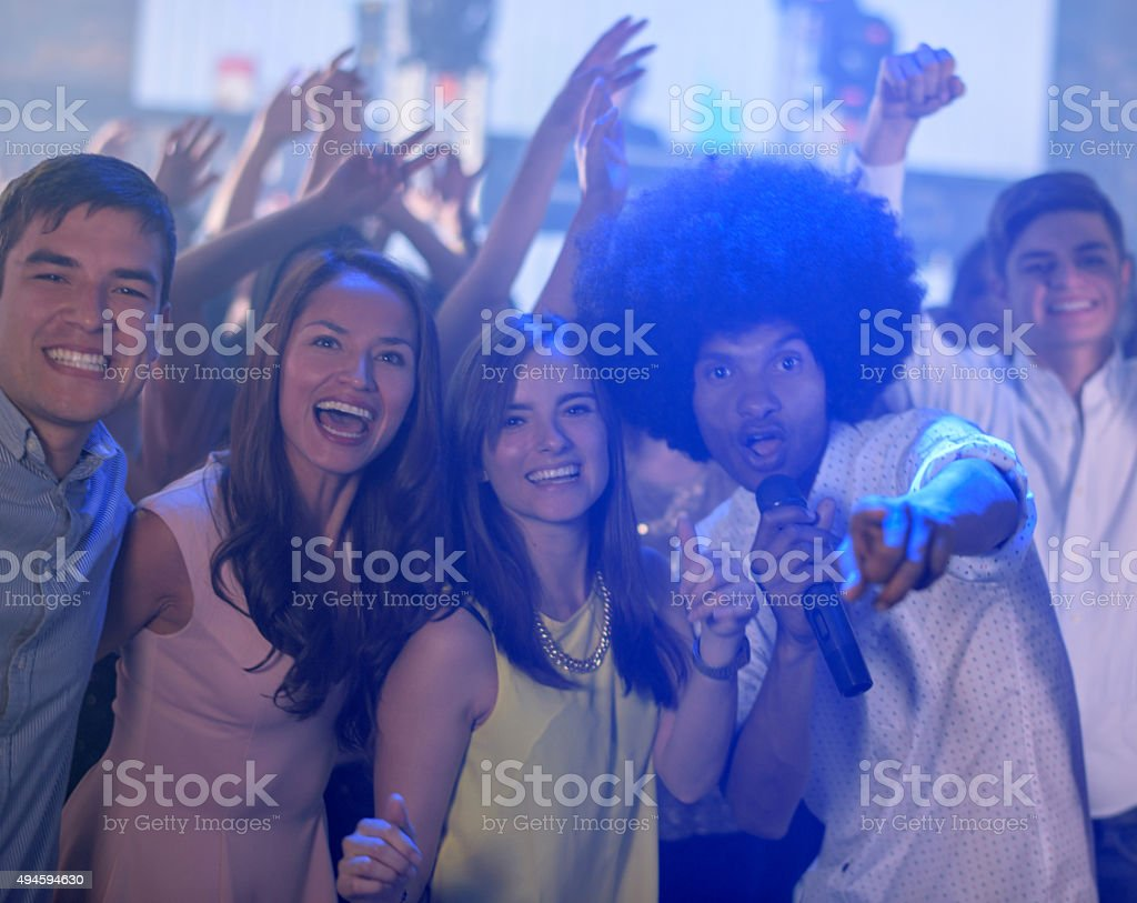 Happy group of friends partying at a karaoke bar stock photo