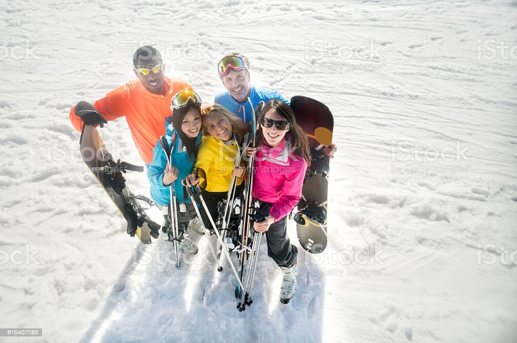 Happy group of friends having fun skiing and snowboarding and looking...