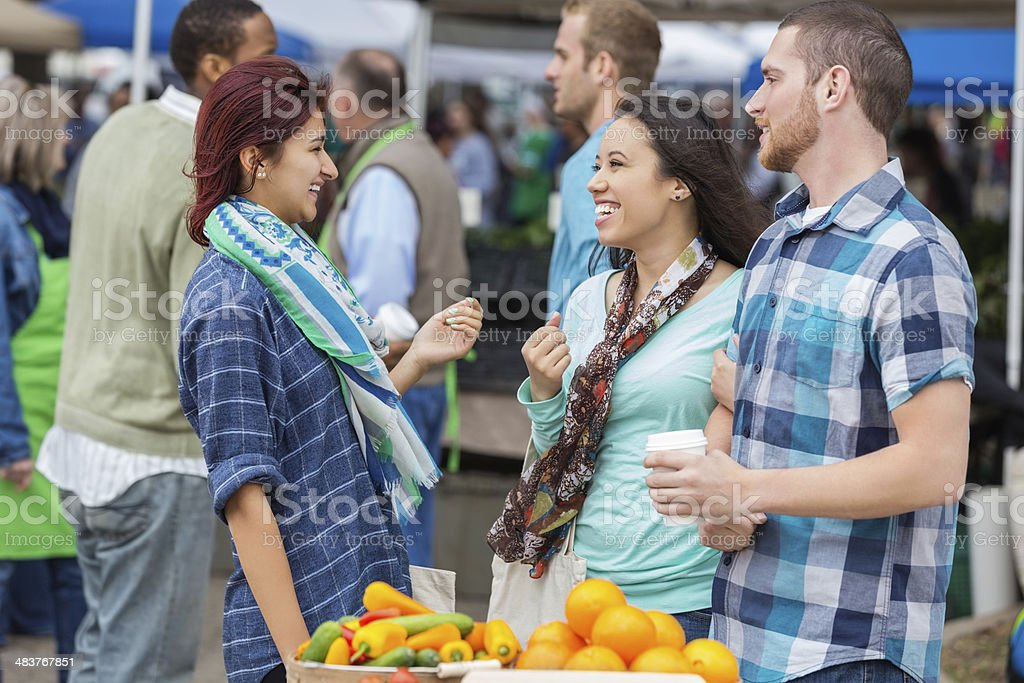 Happy group of friends talking at crowded farmers market stock photo