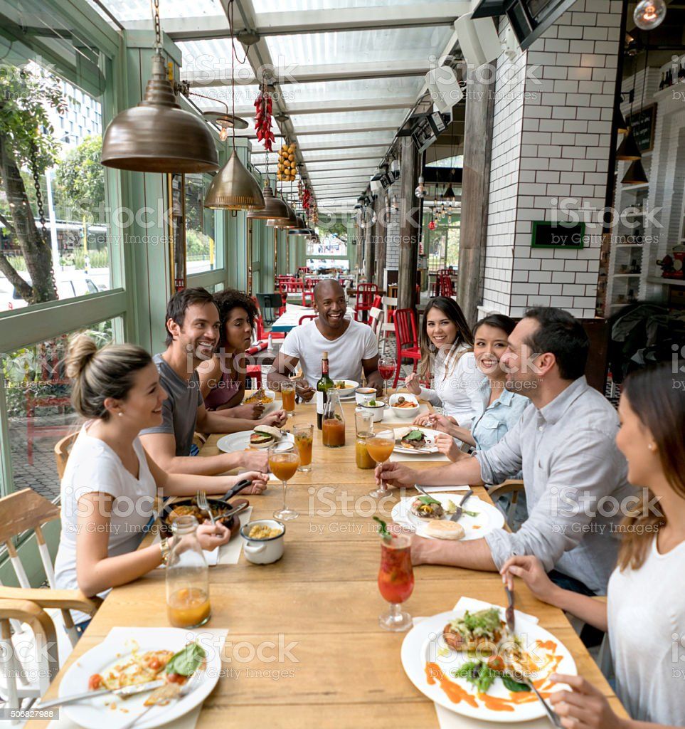 Happy group of people at a restaurant stock photo