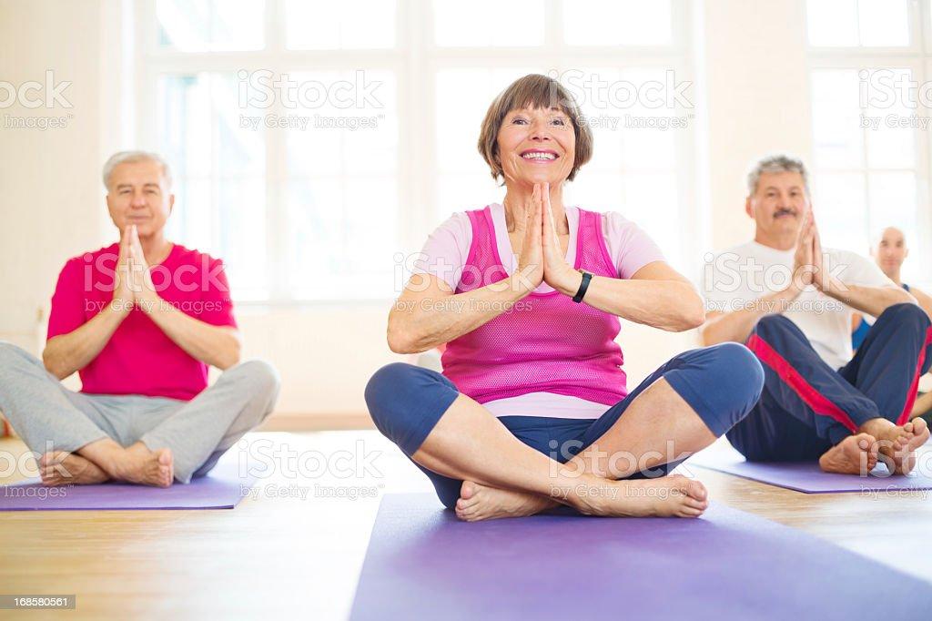 Happy group of seniors doing yoga stock photo
