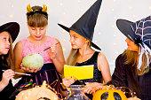 Happy group of teenagers in costumes preparing for Halloween
