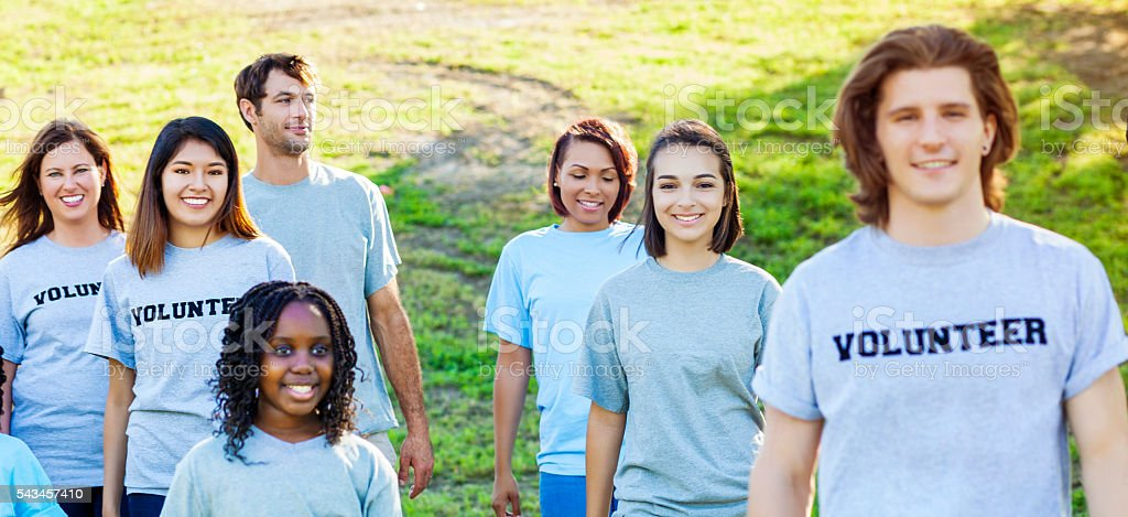 Happy group of volunteers in park stock photo