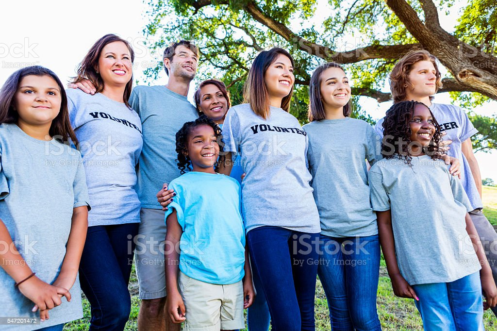 Happy group of volunteers smiling together outside stock photo