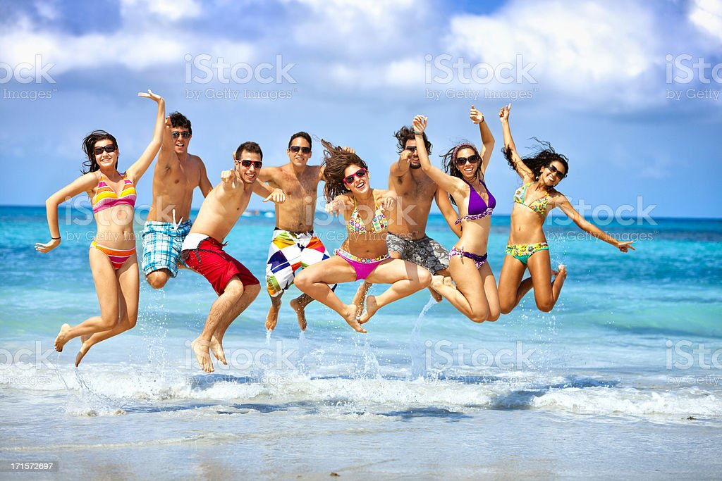 Happy group of young people jumping on a beach party in a tropical...